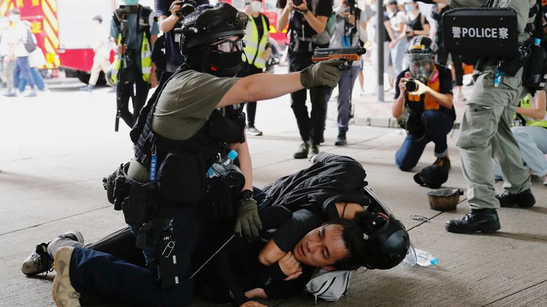 A police officer raises his pepper spray handgun as he detains a man during a march against the national security law at the anniversary of Hong Kong's handover to China from Britain in Hong Kong, China July 1, 2020. REUTERS/Tyrone Siu