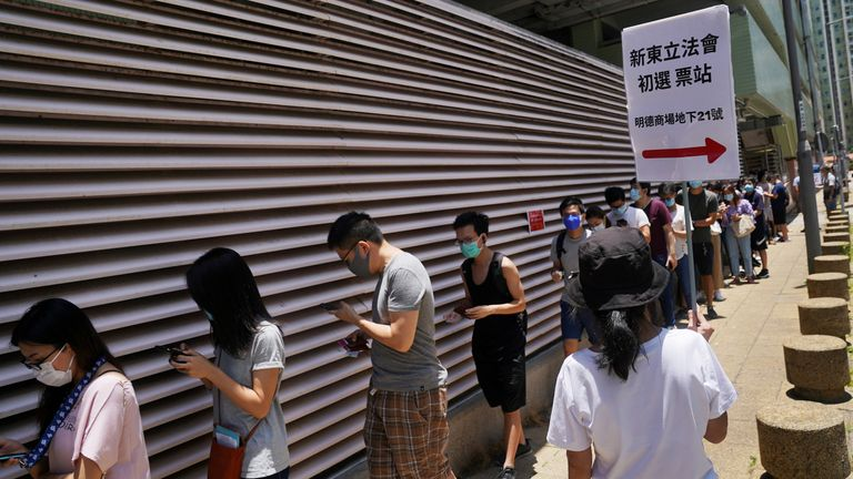 People wearing face masks queued up to vote in 33C heat