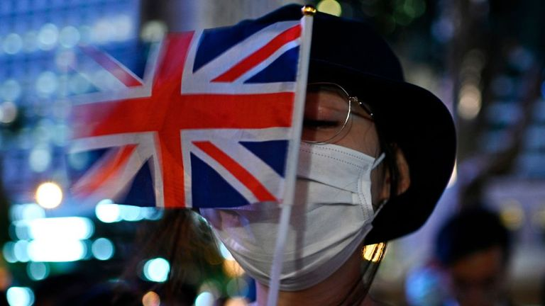 A protester holds the British Union Jack flag as she attends the Stand in Silence for the 74th Anniversary of the Liberation of Hong Kong gathering at the Cenotaph in Hong Kong on August 30, 2019. - Prominent Hong Kong democracy activists including a lawmaker were arrested on August 30 in a protest crackdown -- a move described by rights groups as a well-worn tactic deployed by China to suffocate dissent ahead of key political events. (Photo by Anthony WALLACE / AFP) (Photo by ANTHONY WALLACE/A