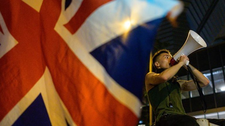 A British Union Jack flag is waved from the ground as a protester uses a loud hailer to speak outside the police headquarters in Hong Kong, early on June 27, 2019. - Hong Kong protesters marched to major consulates on June 26 as they called on G20 nations to confront fellow member China at an upcoming summit in Japan over sliding freedoms in the financial hub. (Photo by Anthony WALLACE / AFP) (Photo by ANTHONY WALLACE/AFP via Getty Images)