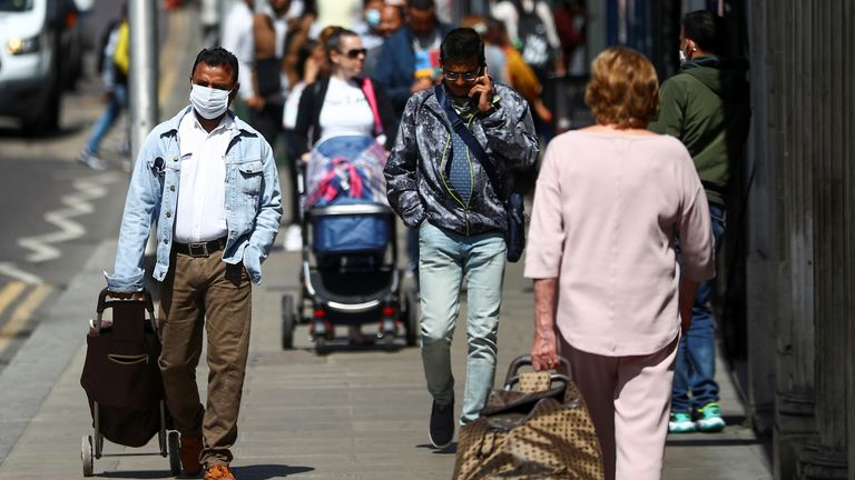 People walk down a street following the coronavirus disease