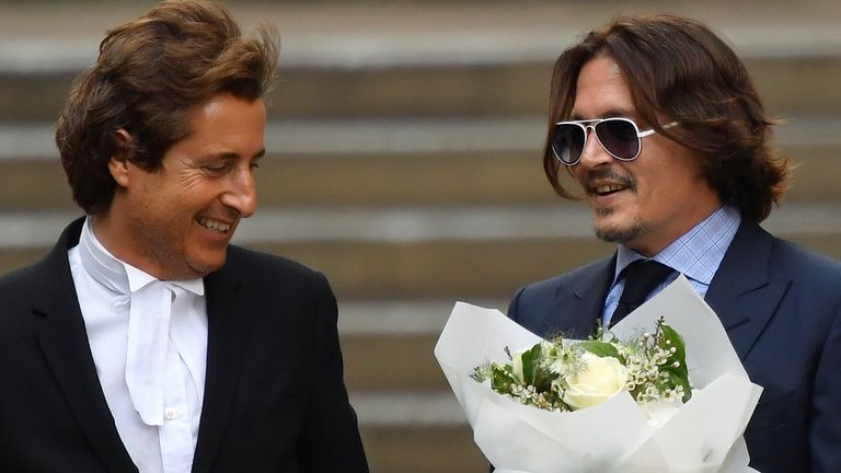 Johnny Depp with flowers, apparently given to him by a fan, and his barrister David Sherborne outside the High Court on July 14