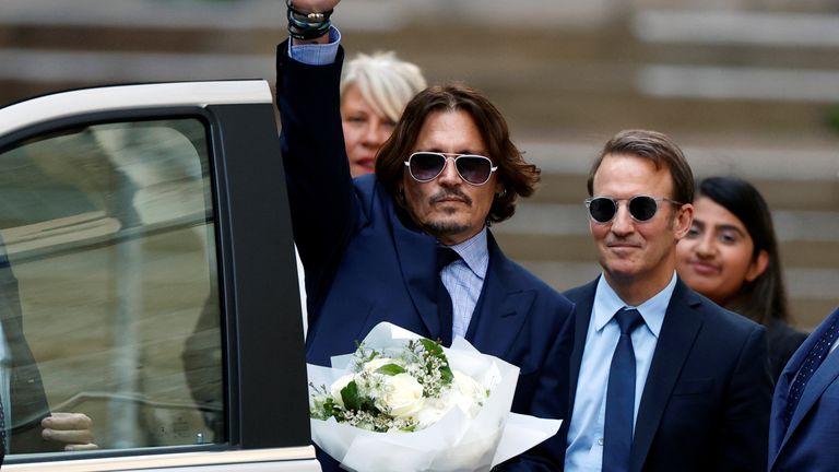 Johnny Depp with flowers, apparently given to him by a fan, outside the High Court on July 14