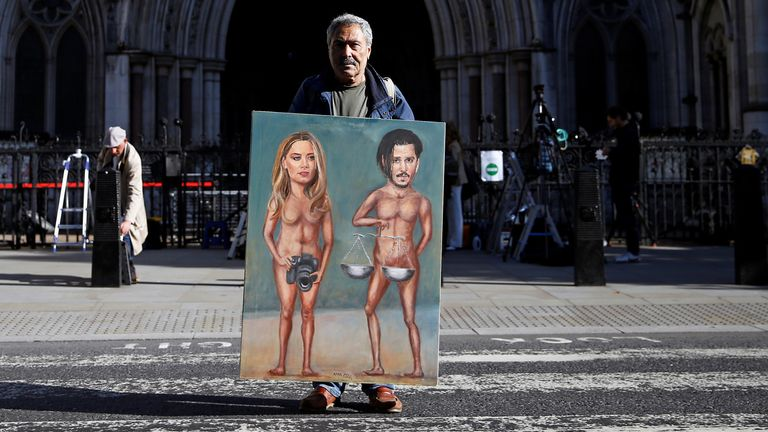 Artist Kaya Mar holds a painting of Depp and Heard outside the High Court