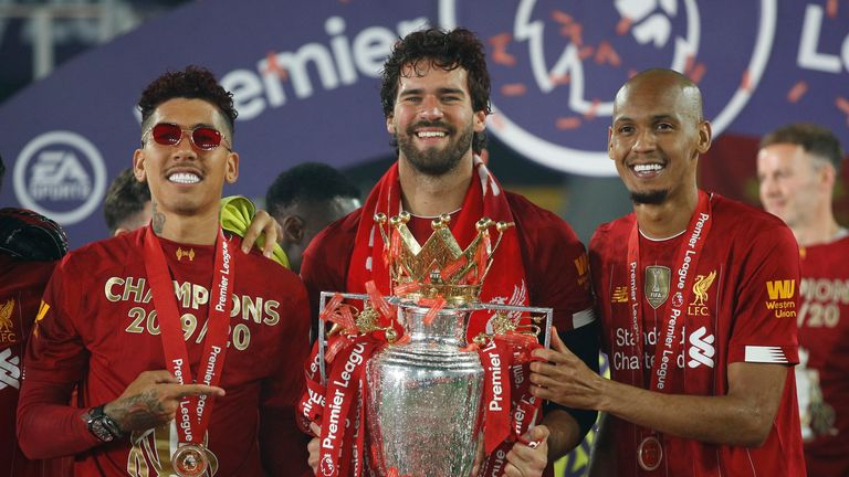 Liverpool's Alisson, Roberto Firmino and Fabinho (right) celebrate with the trophy after winning the Premier League