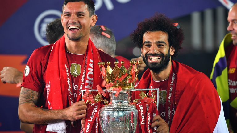 Liverpool players Dejan Lovren and Mo Salah celebrate with the trophy