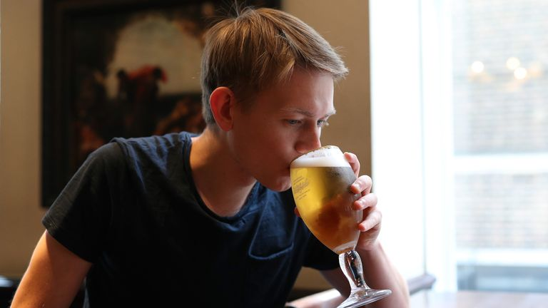 A drinker enjoys a pint in a pub for the first time in more than three months