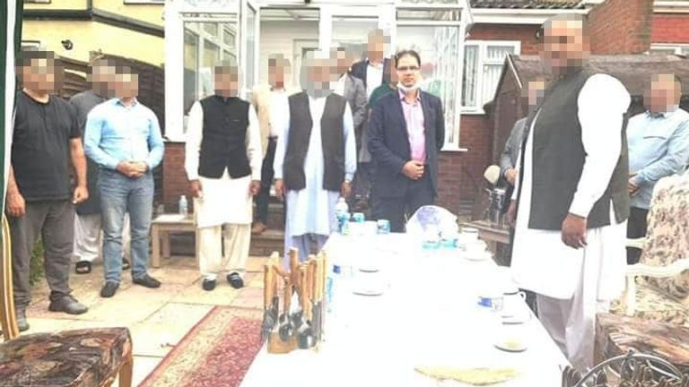 The Mayor of Luton, Tahir Malik, was pictured at the party with his mask hanging below his face