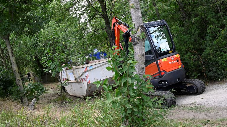 Police carry a container at the site where they started digging in an allotment area near Hanover, Germany July 29, 2020, where Christian B, a suspect in the Madeleine McCann investigation lived for a while some years ago.     REUTERS/Fabian Bimmer