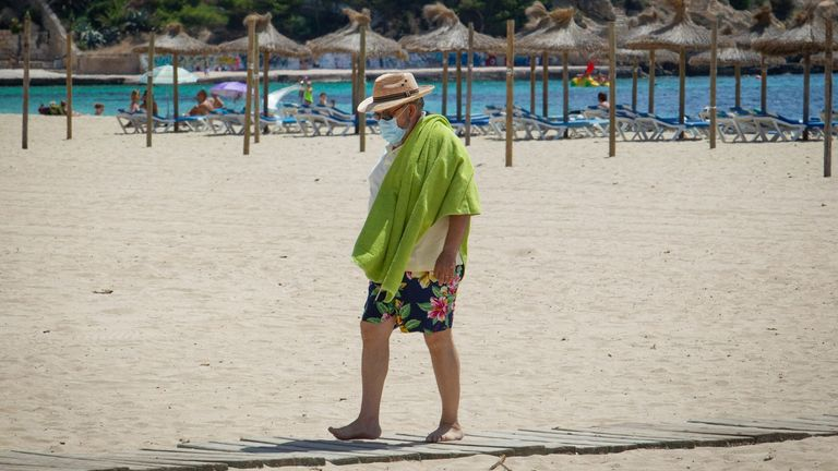 A tourist wearing a face mask walks on Magaluf Beach in Calvia on the Spanish island of Mallorca on July 8, 2020
