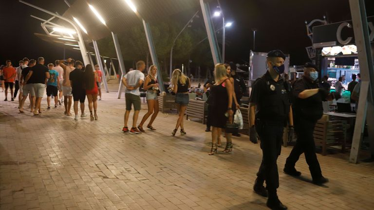 Police officers wearing protective masks patrol in Punta Ballena street in Magaluf