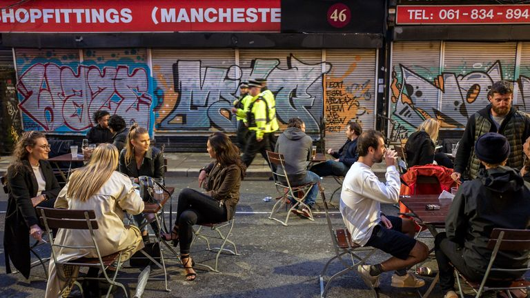 Police officers patrol as bars on Thomas Street in the Northern Quarter set out tables for customers on the closed road on July 04, 2020 in Manchester, England
