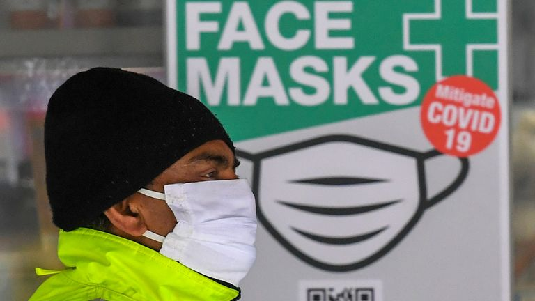 A man wearing a face mask walks past a sign advertising masks in Melbourne on July 20, 2020