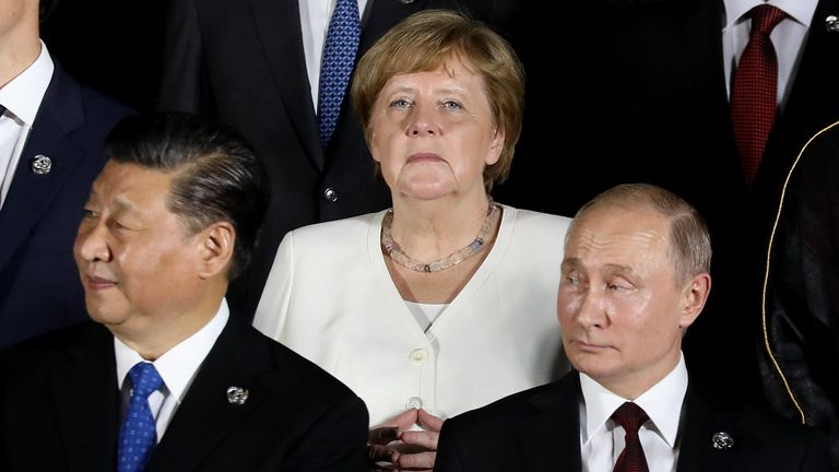 German Chancellor Angela Merkel stands behind Russian President Vladimir Putin (front R) and Chinese President Xi Jinping at the 2019 G20 Osaka summit