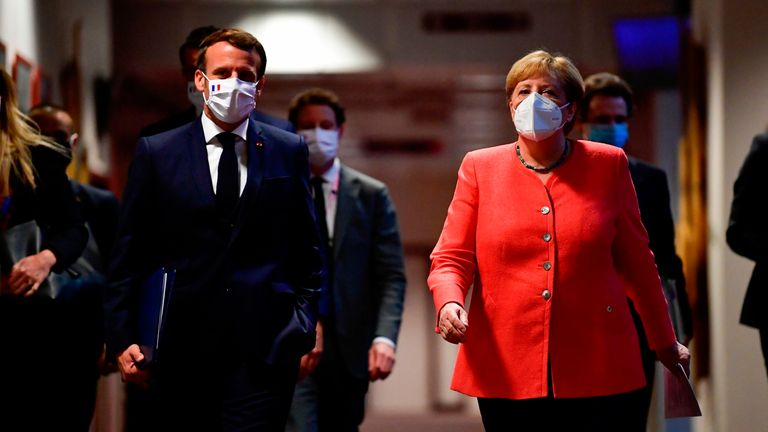 French president Emmanuel Macron and Germany's Angela Merkel prepare for a news conference after the deal was struck