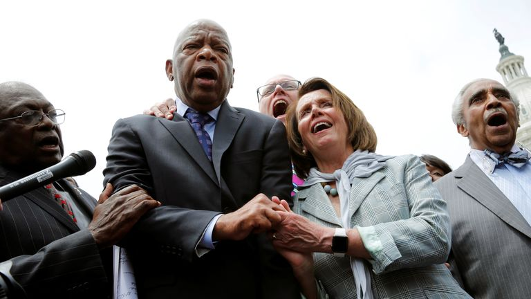 Mr Lewis holds hands with Nancy Pelosi during a sit-in on Capitol Hill over gun-control law