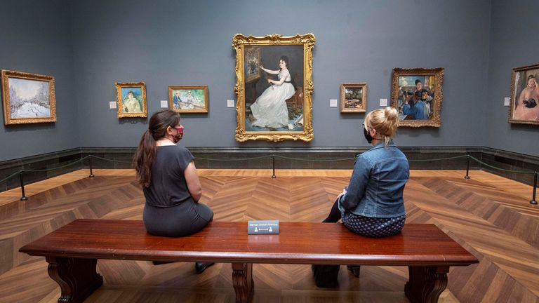 Visitors wearing PPE sit apart as they view Eva Gonzales, 1870, by Edouard Manet, at the National Portrait Gallery, London