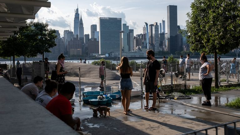 People try to maintain social distance while enjoying a warm and humid day at Gantry Plaza State Park following the outbreak of the coronavirus disease (COVID-19), in Long Island City, New York, U.S., July 25, 2020. REUTERS/Jeenah Moon