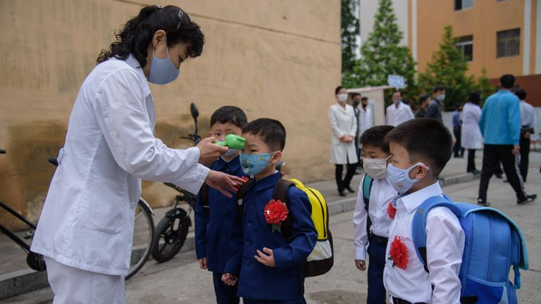 Primary school children wearing face masks as they get their temperature checked in North Korea