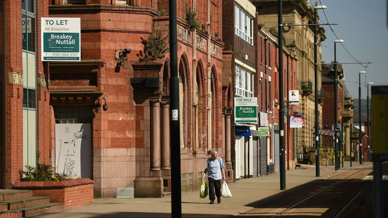 A man walks down a deserted street in Oldham