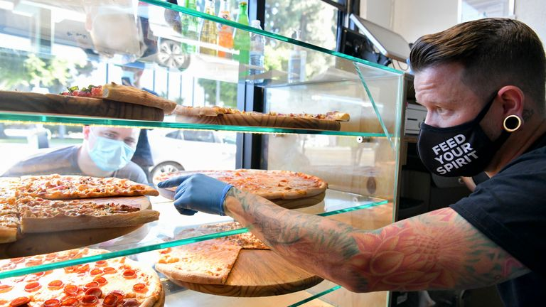 Owner Ben Sales (R) takes orders at Ghost Pizza on July 10, 2020 in Los Angeles, California
