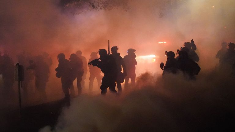 Federal officers use tear gas on a crowd of about 1,000 protesters in front of the Portland courthouse