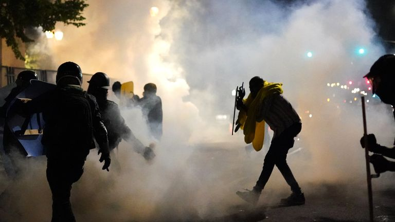 Protesters carry shields through clouds of tear gas during clashes with federal officers