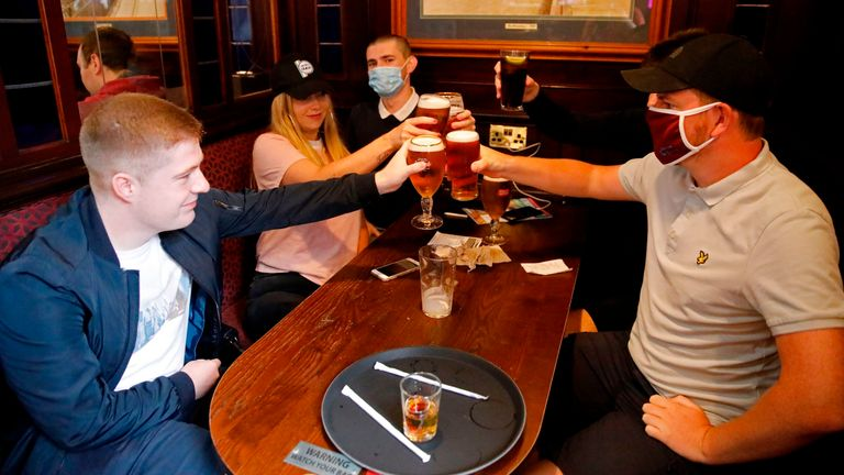 People, some wearing protective face coverings make a toast inside the Wetherspoon pub, Goldengrove in Stratford, London