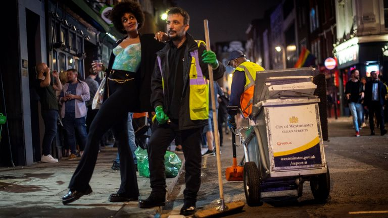 A woman poses with a street cleaner in Soho