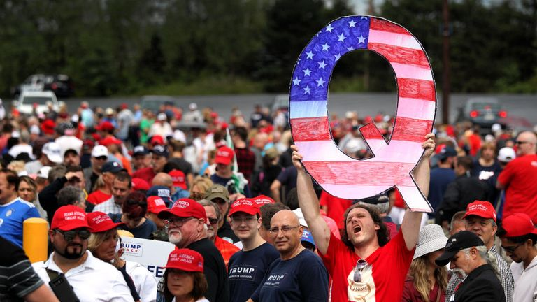 "WILKES BARRE, PA - AUGUST 02: David Reinert holds up a large ""Q"" sign while waiting in line on August 2, 2018 at the Mohegan Sun Arena at Casey Plaza in Wilkes Barre, Pennsylvania to see President Donald J. Trump at his rally. ""Q"" is a conspiracy theory group that has been seen at recent rallies.    (Photo by Rick Loomis/Getty Images)"