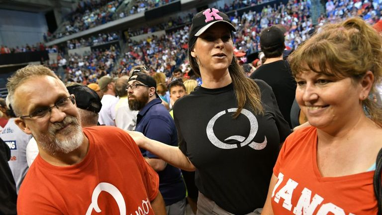"Members of QAnon await the arrival of US President Donald Trump for a political rally at Mohegan Sun Arena in Wilkes-Barre, Pennsylvania on August 2, 2018. - QAnon adheres to a grand-scale conspiracy theory placing President Trump against an alleged ""deep state"" committed to ending his rule. (Photo by MANDEL NGAN / AFP) (Photo credit should read MANDEL NGAN/AFP via Getty Images)"