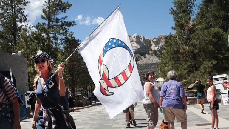 KEYSTONE, SOUTH DAKOTA - JULY 01: A Donald Trump supporter holding a QAnon flag visits Mount Rushmore National Monument on July 01, 2020 in Keystone, South Dakota. President Donald Trump is expected to visit the monument and speak before the start of a fireworks display on July 3. (Photo by Scott Olson/Getty Images)