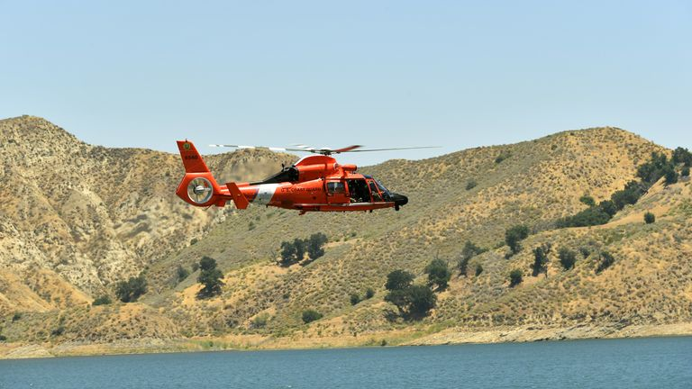 A U.S. Coast Guard helicopter flies over Lake Piru