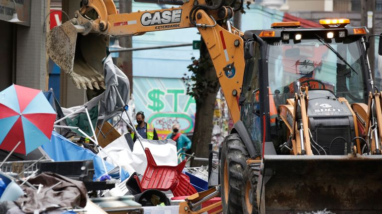 Workers use a bulldozer to remove remaining items from an encampment outside the Seattle Police Department's East Precinct after police cleared the Capitol Hill Occupied Protest (CHOP) in Seattle, Washington on July 1, 2020