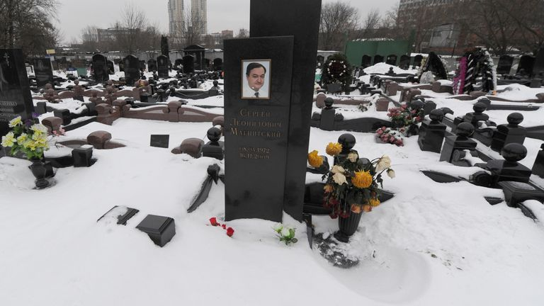 A picture taken on December 7, 2012, shows snow clad grave of Russian lawyer Sergei Magnitsky with his portrait on the tomb (C) at the Preobrazhenskoye cemetery in Moscow.