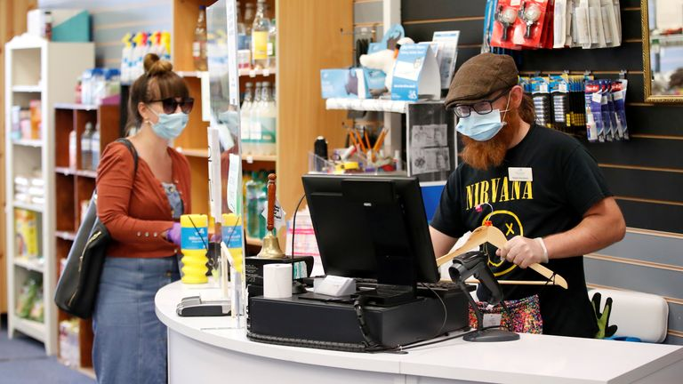 An employee wearing a protective face mask serves a customers at Willen Hospice charity shop