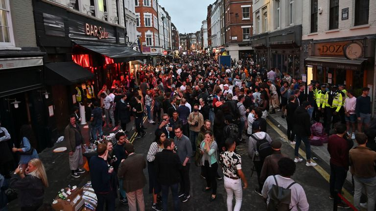 Revellers pack a street outside bars in the Soho area of London on July 4, 2020, as restrictions are further eased during the novel coronavirus COVID-19 pandemic