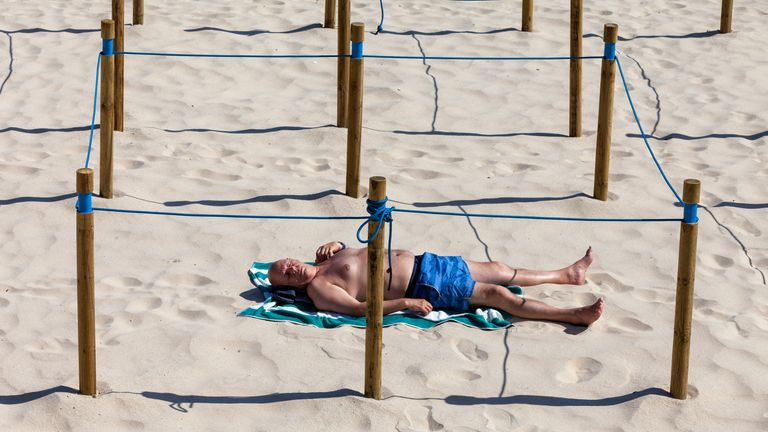 A man sunbathes in a designated isolated spot on a beach in Sanxenxo, Galicia, Spain
