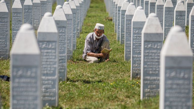 A Bosnian Muslim man reads a religious book between graves