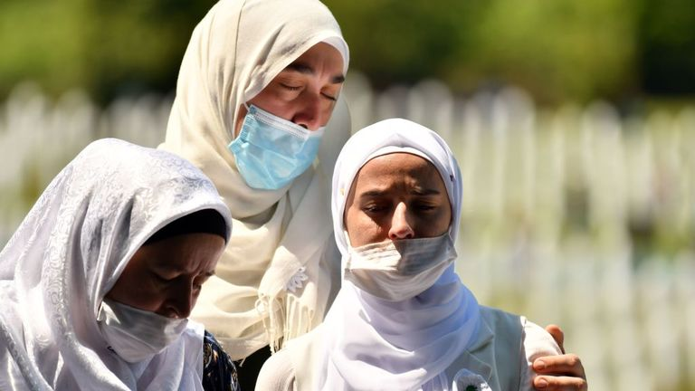 Bosnian Muslim women wearing face masks mourn in front of the casket of a newly identified victim
