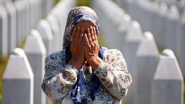 A woman prays at a graveyard, ahead of a mass funeral in Potocari near Srebrenica, Bosnia and Herzegovina