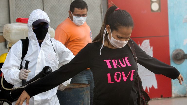 A municipal worker wearing a protective suit disinfects a saleswoman