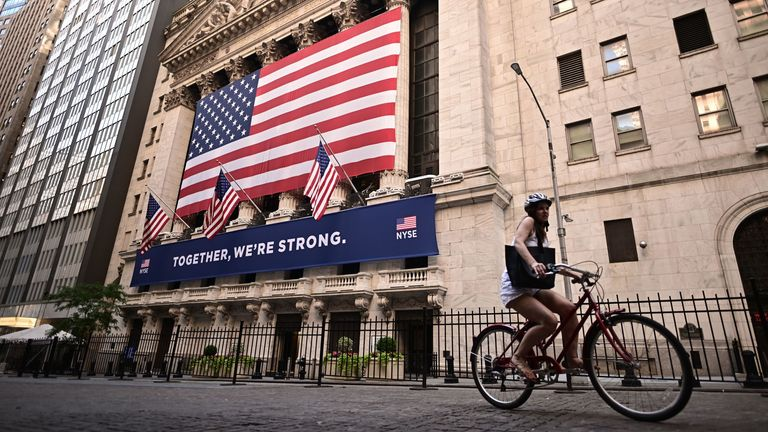 A woman rides past the New York Stock Exchange (NYSE) on July 13, 2020 at Wall Street in New York City.