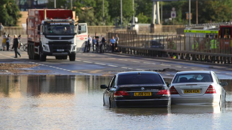 A crowd gathered after a the busy road in northwest London was flooded