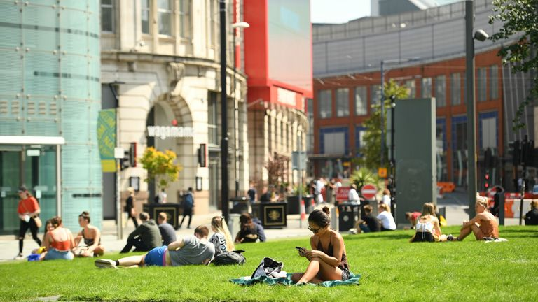 People relax in the warm weather in Manchester