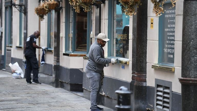 Workers prepare a pub for reopening in London