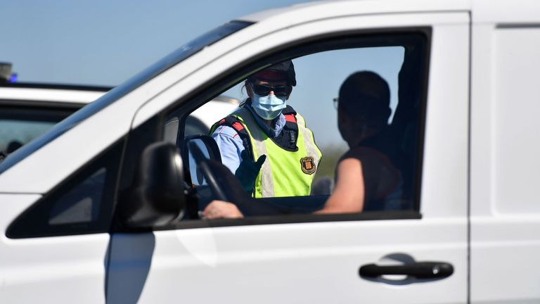 A member of the Catalan regional police force controls a checkpoint on the Corbins highway near Lleida, which is subject to a local lockdown