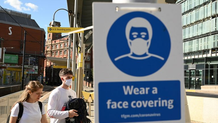 "Pedestrians walk past a sign urging people to 'wear a face covering' due to the COVID-19 pandemic, in Manchester, northwest England on August 3, 2020, following a rise in the number of COVID-19 cases in the region. - Britain on Friday ""put the brakes on"" easing lockdown measures and imposed new rules on millions of households in northern England, following concerns over a spike in coronavirus infections. The government increased regional lockdown measures -- under which people from different households are banned from meeting indoors -- for some four million people across Greater Manchester and parts of Lancashire and Yorkshire. (Photo by Oli SCARFF / AFP) (Photo by OLI SCARFF/AFP via Getty Images)"