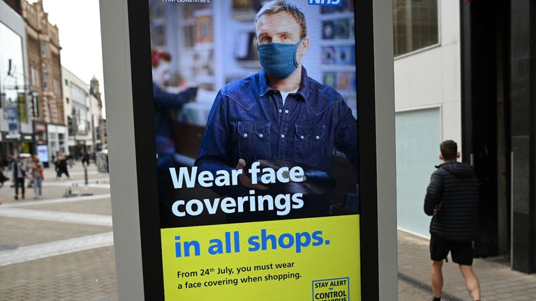A sign calling for the wearing of face coverings in shops is displayed  in the city centre of Leeds, on July 23, 2020, as lockdown restrictions continue to be eased during the novel coronavirus COVID-19 pandemic. - The wearing of facemasks in shops in England will be compulsory from Friday, but full guidance is yet to be published. (Photo by Oli SCARFF / AFP) (Photo by OLI SCARFF/AFP via Getty Images)