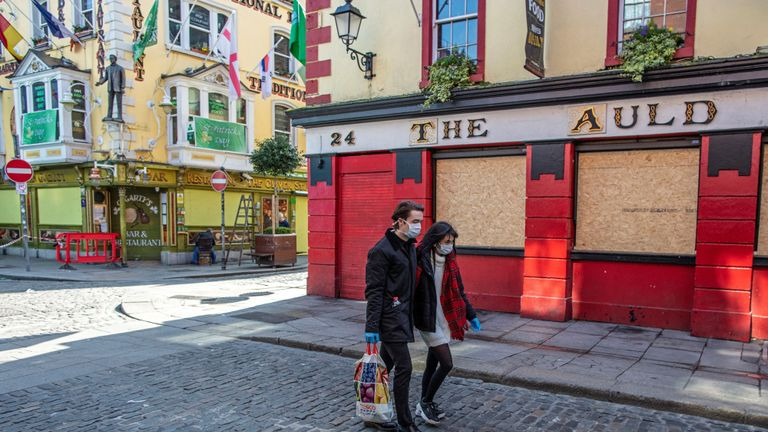 "People wearing face mask as a precautionary measure against Covid-19, carry a shopping bag as the pass a boarded-up and temporarily closed pub in Dublin, on March 25, 2020, after Ireland introduced measures to help slow the spread of the novel coronavirus. - Ireland's prime minister Leo Varadkar on Tuesday announced that all non-essential businesses will shut from midnight  as part of the country's latest measures to tackle the coronavirus outbreak. ""These are unprecedented actions to respond to an unprecedented emergency,"" he said, adding the measures would remain in place until at least April 19. (Photo by PAUL FAITH / AFP) (Photo by PAUL FAITH/AFP via Getty Images)"